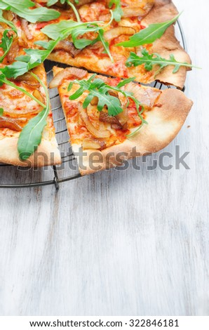 Thin crust pizza slice topped with fresh rocket and caramelised onions  - stock photo