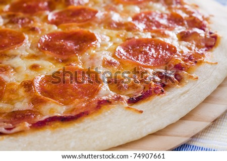 Thin crust pizza topped with pepperoni slices and mozzarella cheese.