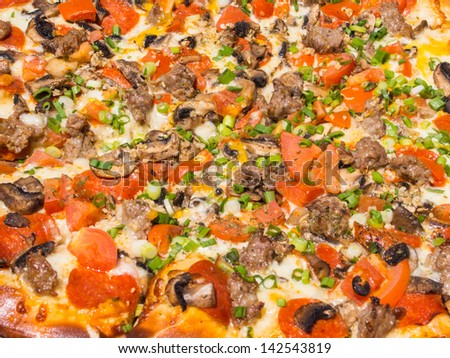 Thin crust pizza with various toppings and melted cheese. - stock photo