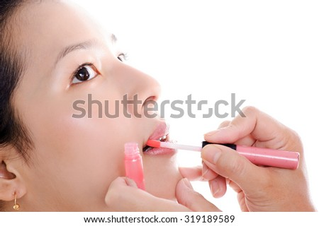Thin focus at lip Beautiful young woman apply pink lipstick on white background.