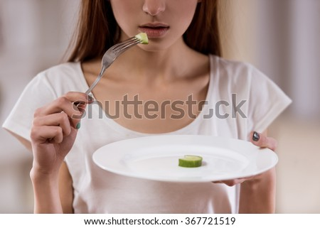 Thin girl with an empty plate standing in the center of the room closeup, malnutrition harms health. - stock photo