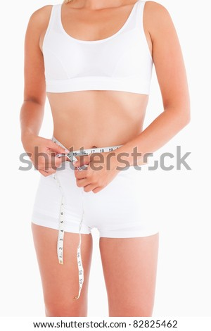 Thin lady measuring her waist in a studio