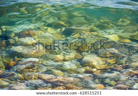 Thin layer of limpid sea water over the stony bottom.Water background