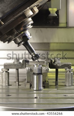Thin mill installed in spindelhead cutting the metal blank fixed in attachment - stock photo