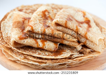 Thin pancakes, crepes with caramel syrup on round wooden  cutting board. Pancake day, mardi gras, maslenitsa background. Isolated. - stock photo