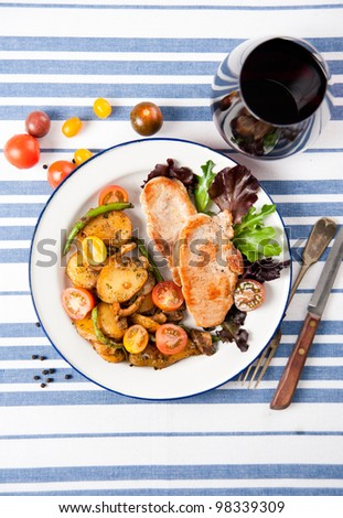 Thin Pork Chops Served with Sauteed Potatoes, Green Beans and Greens - stock photo