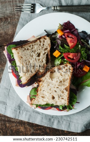 Thin sliced ham and vegetables on rustic crusty fresh country bread