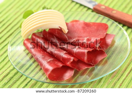 Thin slices of dried meat and butter - stock photo