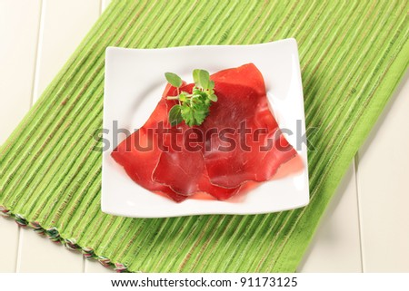 Thin slices of dried meat on a square plate - stock photo