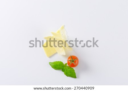 thin slices of parmesan cheese, cherry tomato and basil on white background - stock photo