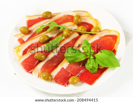 Thin slices of prosciutto crudo and marinated green olives - stock photo
