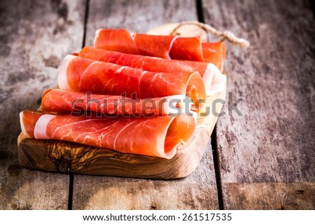 thin slices of prosciutto on wooden cutting board - stock photo
