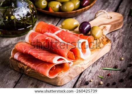 thin slices of prosciutto with mixed olives on wooden cutting board - stock photo