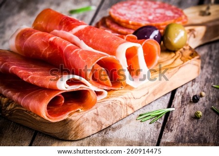 thin slices of prosciutto with olives and salami on wooden cutting board - stock photo
