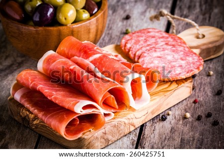 thin slices of prosciutto  with salami and olives on wooden cutting board - stock photo