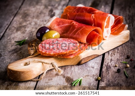 thin slices of prosciutto with salami, olives and rosemary on wooden cutting board - stock photo