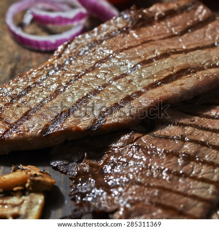 thin steak cooked with onion  - stock photo