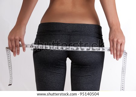Thin Woman measuring butt and hips - stock photo