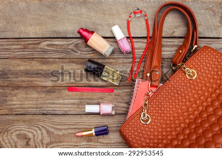 Things from open lady handbag. women's purse on wood background. Toned image.   - stock photo