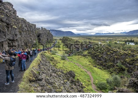 Thingvellir, Iceland - August 30 2016: Hoards of tourists taking selfies on the tectonic plate boundary where Europe is moving away from America.  Europe can be seen in the background.