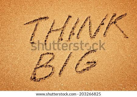 Think BIG phrase written on sand - stock photo
