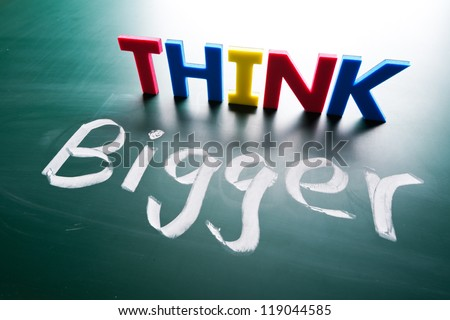 Think bigger concept, words on blackboard - stock photo