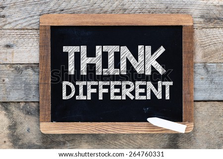 Think different Sign. Think different Sign on blackboard on wooden background - stock photo