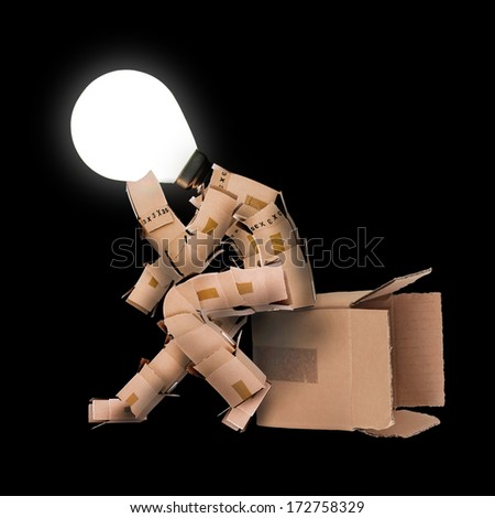Think outside the box concept with a boxman character and a  light bulb head on a black background - stock photo
