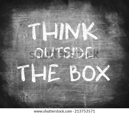 Think outside the box handwritten on chalkboard  - stock photo