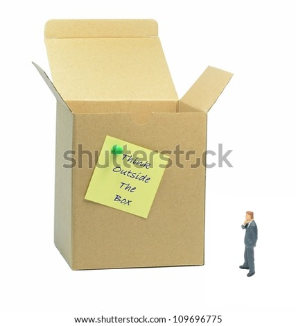 Think outside the box metaphor with businessman looking at box - stock photo