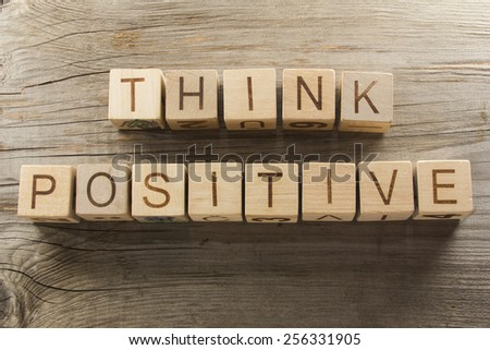 Think positive text on a wooden blocks on a wooden background - stock photo