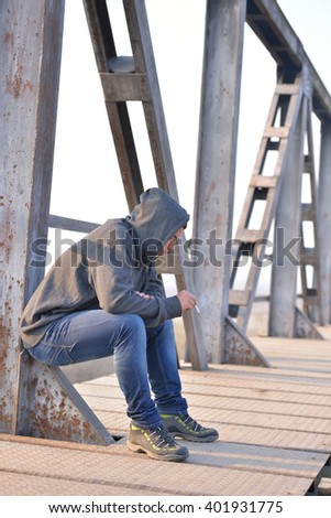 Thinker teenager in depression sitting down on the bridge at the sunset. Concept of teenage problems. Unhealthy habits - stock photo