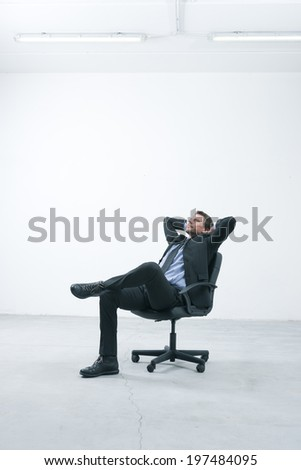Thinkful businessman sitting on office chair with hands behind head in his new empty office. - stock photo