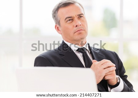 Thinking about business. Thoughtful mature man in formalwear holding hands clasped and looking away while sitting at his working place - stock photo