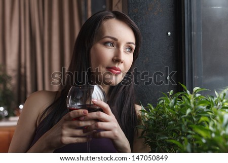Thinking about him. Thoughtful middle-aged women standing with a glass of wine and looking away - stock photo