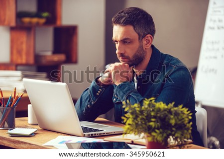 Thinking about solution. Concentrated young man looking at his laptop while sitting at his working place in office - stock photo