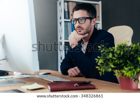 Thinking about solution. Thoughtful young man in smart casual wear holding hand on chin and looking at computer monitor while sitting at his working place in office - stock photo