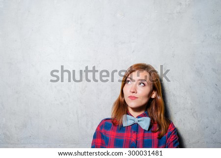 Thinking about solutions. Thoughtful cute young woman in plaid shirt looking up. - stock photo