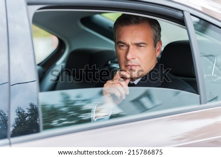 Thinking about solutions. Thoughtful mature businessman holding hand on chin and looking away while sitting on the back seat of a car  - stock photo