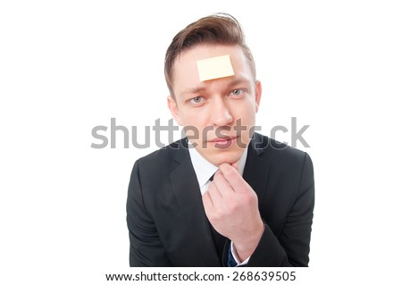 Thinking about solutions. Thoughtful young businessman with empty sticker on his forehead holding hand on chin isolated on white. - stock photo