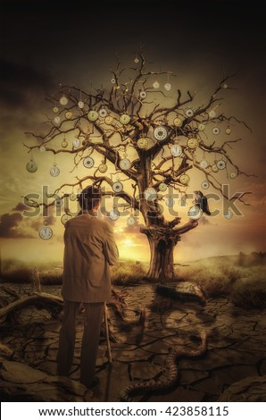 thinking about the past, middle-aged man standing against a tree with a pocket watch - stock photo