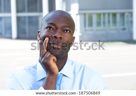 Thinking african businessman in front of his office - stock photo