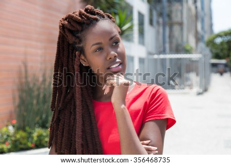 Thinking african woman with dreadlocks in the city - stock photo