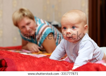 Thinking baby with his grandmother on a bed - stock photo