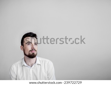 Thinking beard man isolated on white background. Closeup portrait of a casual young pensive businessman looking up at copyspace Caucasian male model Guy looking up. Portrait of a pensive young student - stock photo