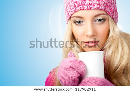 thinking beautiful blonde woman holding white cup of drink over blue - stock photo