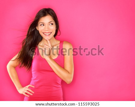 Thinking beautiful young woman looking to the side at pink copyspace. Funky fresh and playful multiracial Asian Chinese / Caucasian smiling happy and joyful on pink background. - stock photo