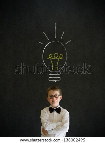 Thinking boy dressed up as business man with bright idea chalk background lightbulb on blackboard background - stock photo