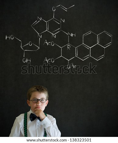 Thinking boy dressed up as business man with science or chemistry formula on blackboard background - stock photo