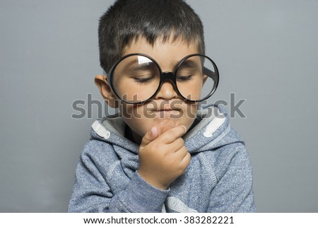 thinking, boy with big glasses very serious and thinking
